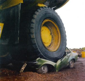 634px-Haul_truck_backed_over_a_parked_vehicle-300x284